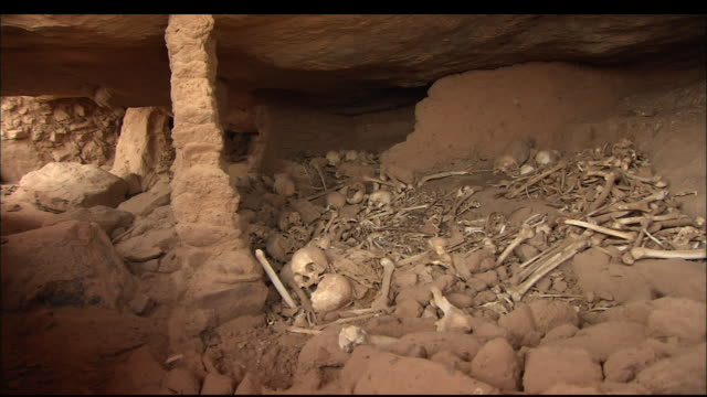 human bones lie piled in a cave. available in hd. - bone stock videos & royalty-free footage