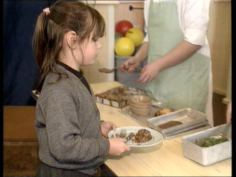 vídeos de stock e filmes b-roll de human bse/cjd link statements; itn lib england: wood street infants school tms beef burgers on tray in school canteen pull out as dinner lady serves... - pie humano