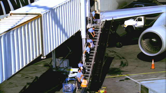 ws, ha, human chain of ground crew handing parcels up staircase towards aircraft, los angeles, california, usa - fluggastbrücke stock-videos und b-roll-filmmaterial