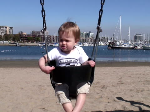 human development: play, balance on playground swing - endast en pojkbaby bildbanksvideor och videomaterial från bakom kulisserna