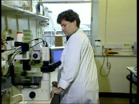 Parliament vote ITN ENGLAND London Scientist in white coat removing tray of cellular samples from fridge cabinet MS Scientist along to sit down at...