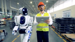 Human factory worker and a robot are walking together in factory premises