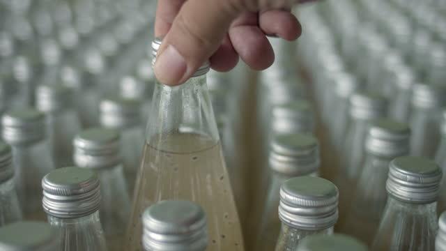 vidéos et rushes de main humaine vérifiant les bouteilles dans la ligne sur le récipient, plan rapproché - groupe d'objets