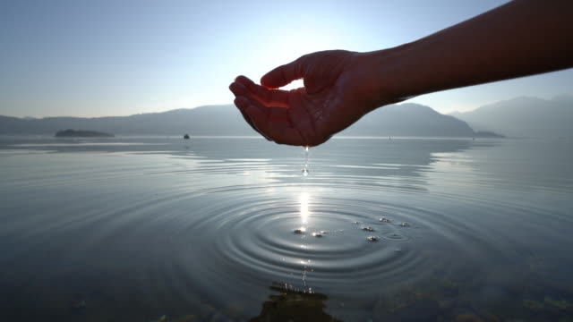 Human hand cupped to catch fresh water from lake