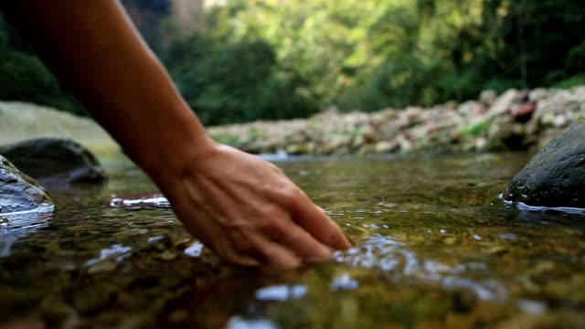 Human hand cupped to catch fresh water from river