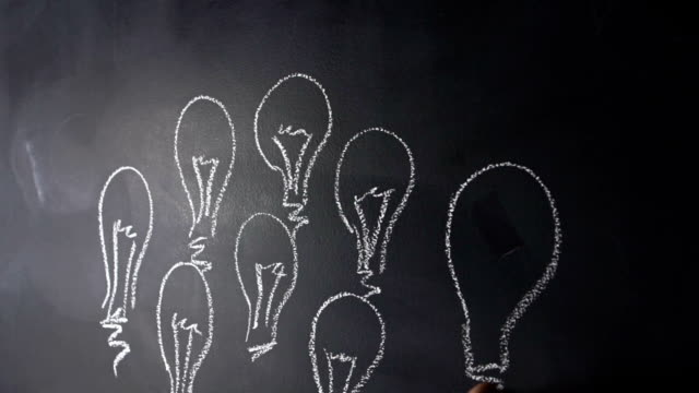 Human hand drawing lightbulbs on blackboard