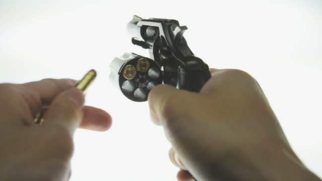 CU Human hand filling bullets in cylinder of colt revolver and placing it on light table / Los Angeles, California, USA
