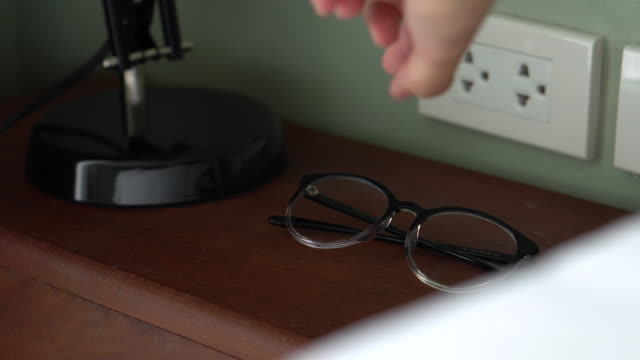 human hand finding for glasses at the nightstand - electrical plug stock videos & royalty-free footage