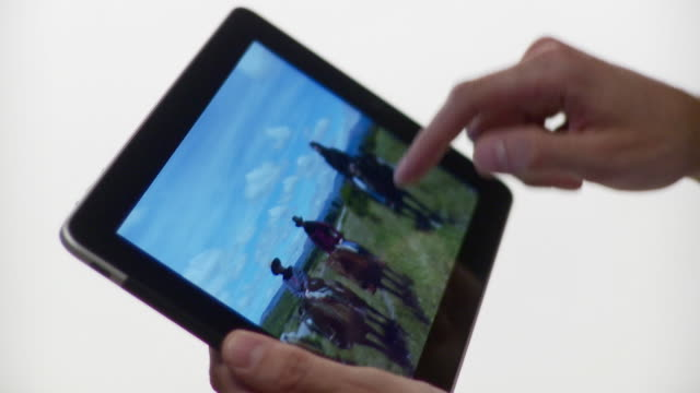 CU Human hand flipping photos horizontally on tablet computer / Brooklyn, New York, USA