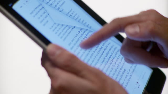 cu human hand flipping through pages of electronic book on tablet computer / brooklyn, new york, usa  - 讀 個影片檔及 b 捲影像