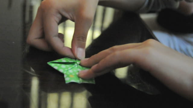 cu human hand folding piece of flowered green origami paper on table / los angeles, california, usa - folding paper stock videos and b-roll footage