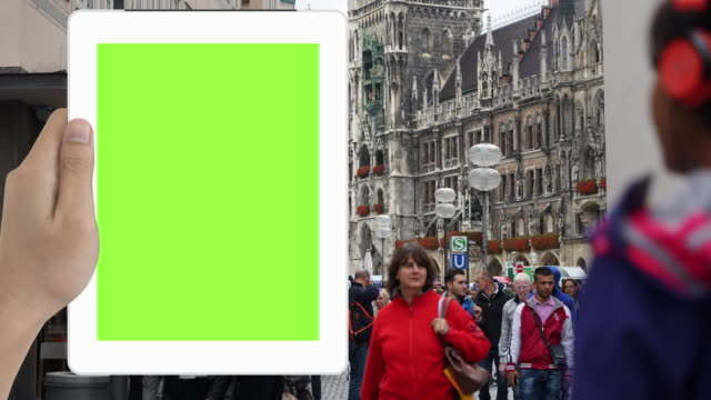 Human hand holding Green Screen tablet in Paris tourist location