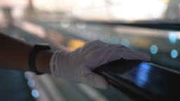 Human hand in plastic glove holding  Escalator handle in covid-19 corona virus situation in public space