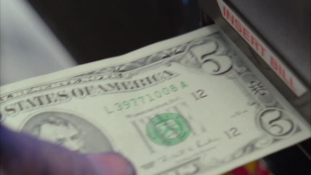 cu human hand inserting us five dollar bill into slot machine / las vegas, nevada, usa - 5ドル米国紙幣点の映像素材/bロール
