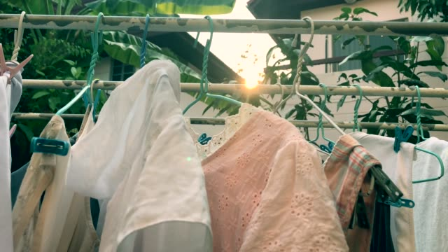 human hand keeping clothing drying on clothes rack , scene with sun flare , birdsong surrounding - drying rack stock videos and b-roll footage