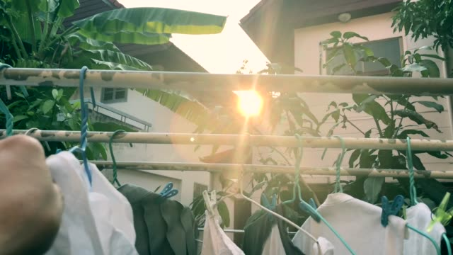human hand keeping clothing drying on clothes rack , scene with sun flare , birdsong surrounding - washing line stock videos & royalty-free footage