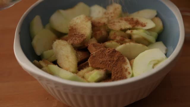 cu human hand mixing cinnamon and brown sugar in apple slices / london, uk - cinnamon stock videos & royalty-free footage