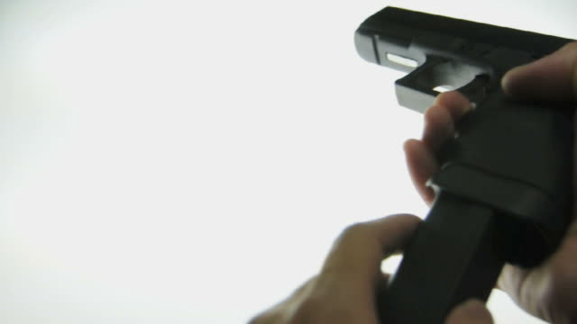 CU Human hand picking up Glock 22c semi automatic pistol and inserting magazine / Los Angeles, California, USA