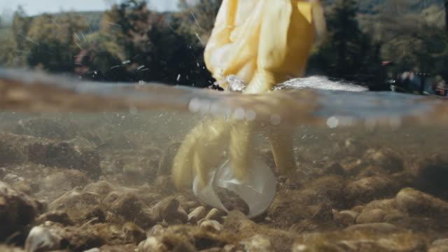 mano umana che raccoglie vetro di plastica dal fiume - pulizia dell'ambiente video stock e b–roll