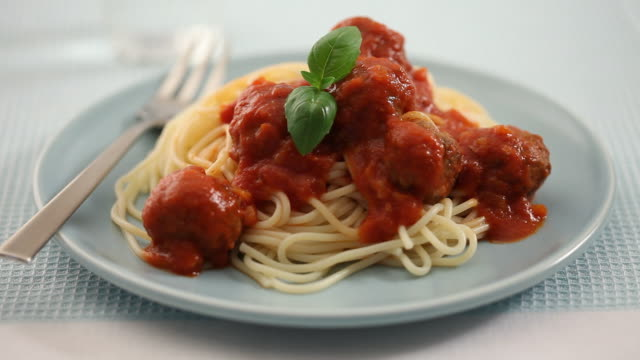 cu pan human hand placing basil on top of meatballs / london, uk - spaghetti stock videos & royalty-free footage