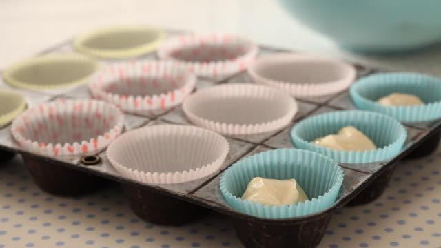 CU Human hand placing cupcake mix in cupcake cases / London, UK