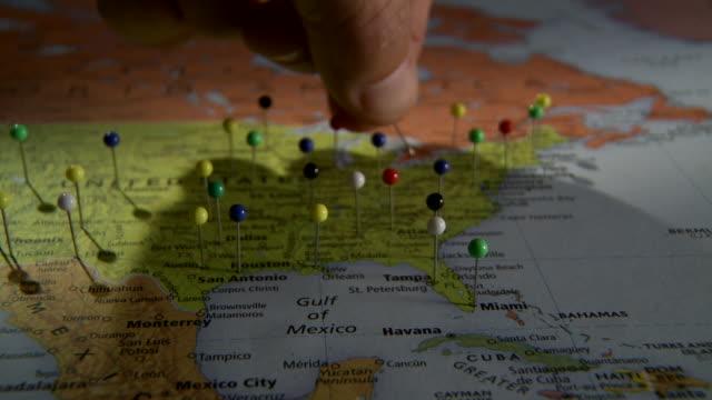 cu human hand placing push pin in map of north america / atlanta, georgia, usa - 画鋲点の映像素材/bロール