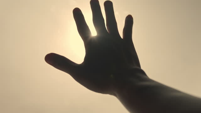 slo mo human hand playing with sunlight - back lit stock videos & royalty-free footage