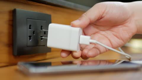vídeos y material grabado en eventos de stock de mano humana enchufe el cargador de la batería del teléfono para el uso de teléfono móvil - cargar