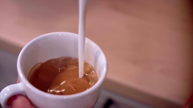 vídeos de stock, filmes e b-roll de human hand pouring milk into coffee/ debica/ poland - barista