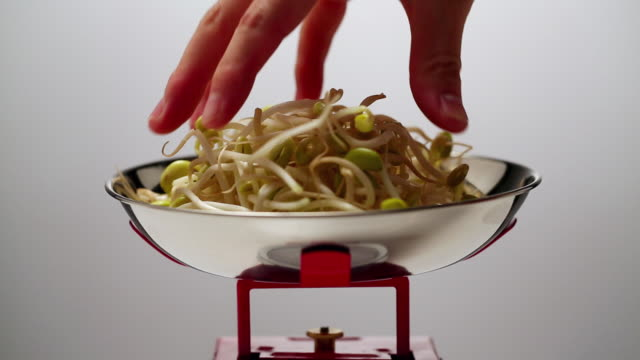 ECU Human hand putting bean sprout onto bowl / Seoul, South Korea
