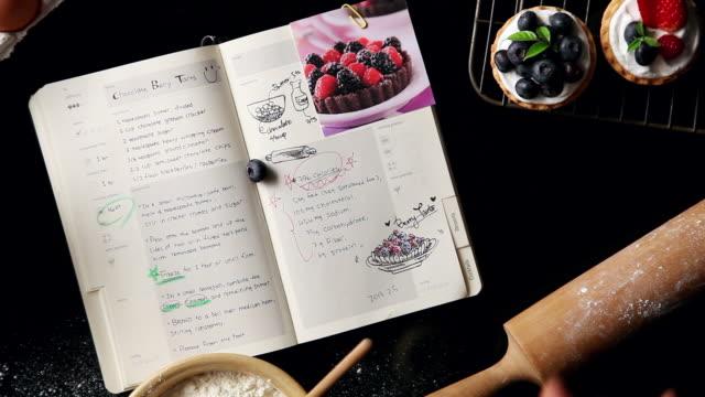 vídeos de stock, filmes e b-roll de cu human hand removing tart next to diary / seoul, south korea - receita