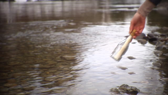 ms human hand throwing message in bottle into river / vancouver, british colombia, canada - bottiglia video stock e b–roll