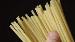Human hand touches a pile of a spaghetti