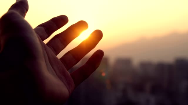 human hand touching light of sun - harmony stock videos & royalty-free footage
