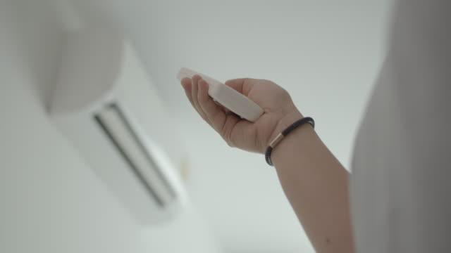 人間の手は、リモコンからエアコンをオフに,シフトフォーカス - エアコン点の映像素材/bロール