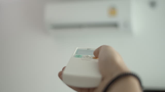 人間の手は、リモコンからエアコンをオンに、シフトフォーカス - エアコン点の映像素材/bロール