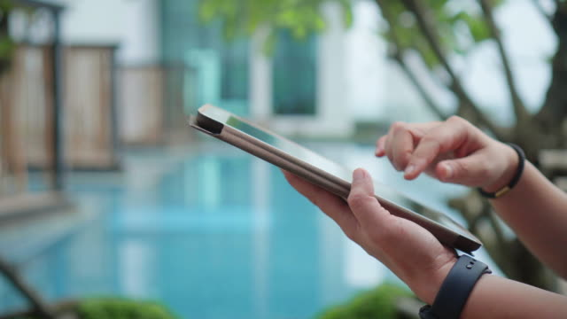 human hand using digital tablet near pool,close-up - summer reading stock videos & royalty-free footage