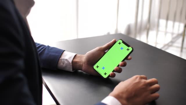 vidéos et rushes de main de l'homme à l'aide de téléphone portable à écran vert dans le bureau, iphone x - mobilité