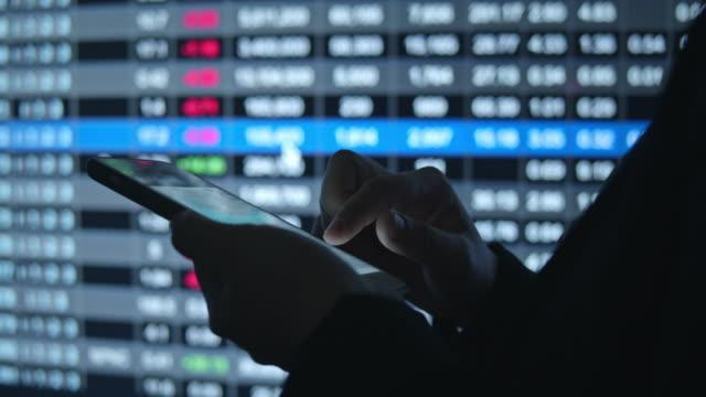 vidéos et rushes de main humaine utilisant le smartphone devant l'écran financier de marché boursier - échange commercial