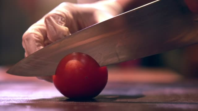 human hand with glove cutting vegetables on a chopboard with knife tomato chopping accuracy skill - cutting stock videos & royalty-free footage