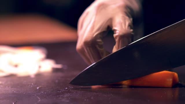 menschliche hand mit handschuh schneiden gemüse auf einem chopboard mit messer karotten hacken genauigkeit fähigkeit - schneidebrett stock-videos und b-roll-filmmaterial