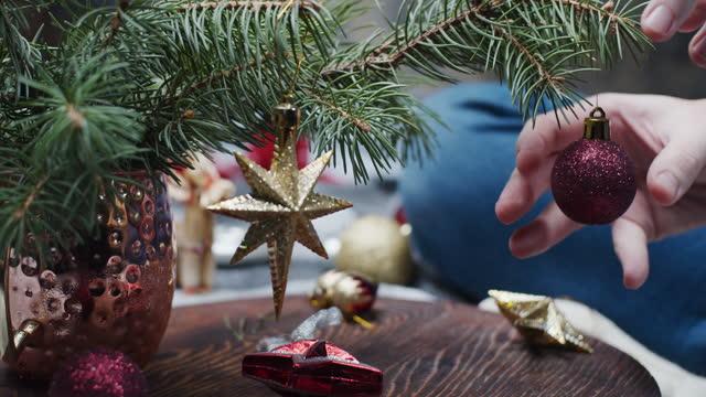 vídeos de stock e filmes b-roll de human hands are decorating christmas tree - enfeitar a árvore de natal