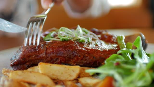 Human hands cutting beef steak