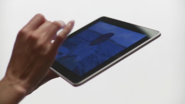 CU Human hands flipping photos horizontally on tablet computer / Brooklyn, New York, USA