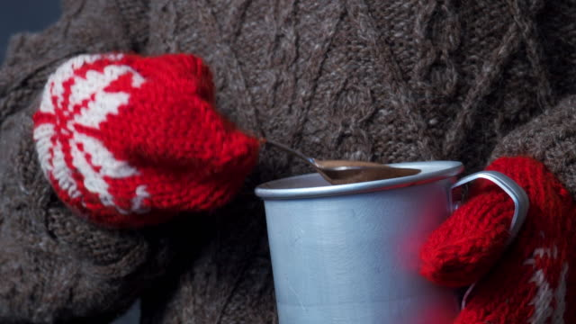 human hands in red mittens holding mug of hot chocolate - mitten stock videos and b-roll footage