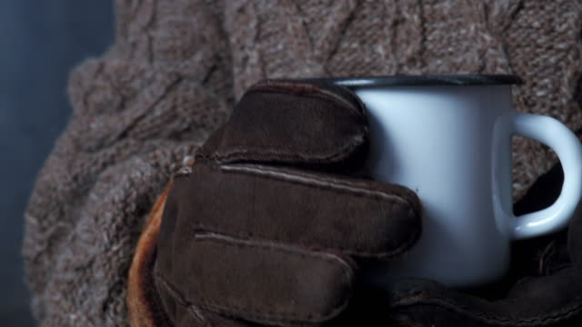 human hands in suede gloves holding mug of hot drink - leather stock videos & royalty-free footage