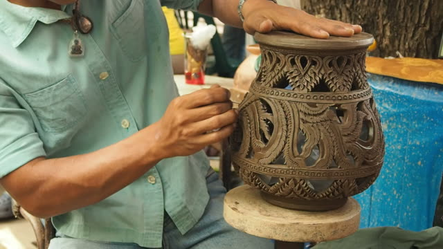 human hands making clay pot on a potter's wheel