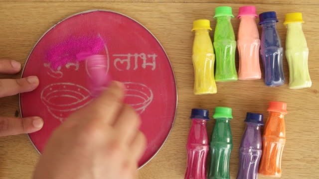 human hands prepare a pre-cut stencil of a diya, lamp of oil, for the celebrations of diwali on the floor with coloured powder - stencil stock videos & royalty-free footage
