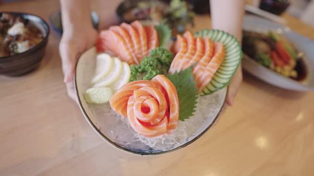 human hands presenting beautiful platter of salmon sashimi. - omega 3 stock videos & royalty-free footage