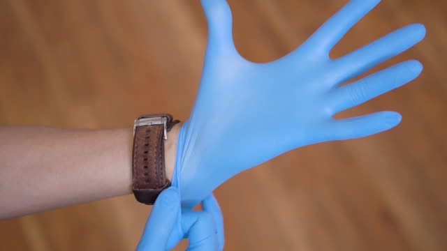 human hands putting on medical rubber gloves - glove video stock e b–roll